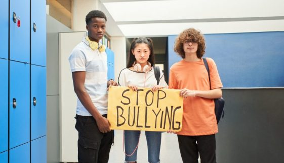 A group of students display a banner with the phrase: Stop Bullying.